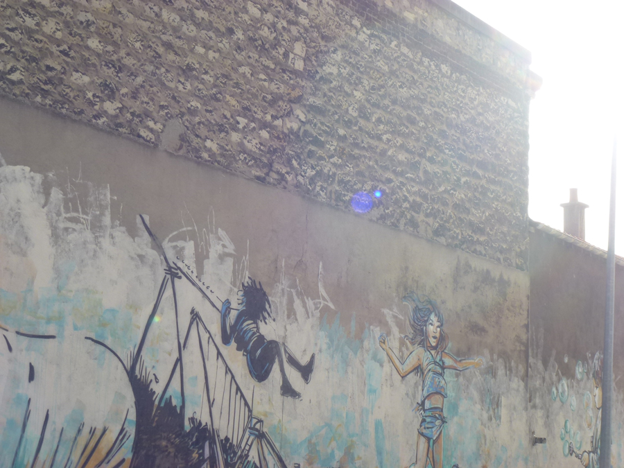 balançoire dessinée au pochoir sur un mur en briques